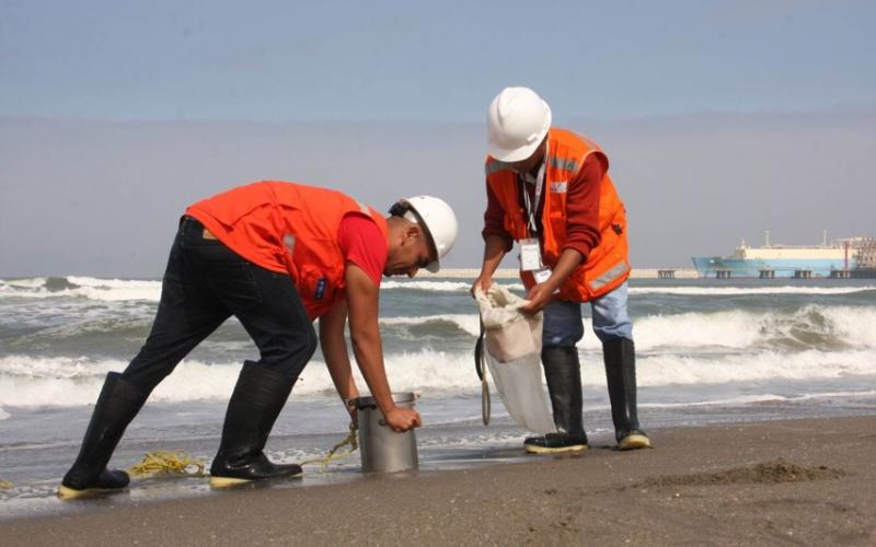 Two people sampling benthos on a beach in Peru